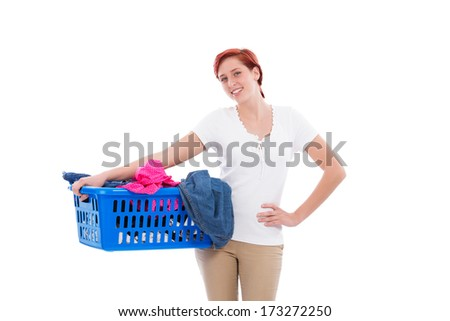 happy redhead woman with her laundry in a blue basket