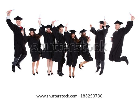 Happy rejoicing group of multiethnic graduates leaping in the air cheering as they celebrate the successful completion of their academic studies  isolated on white - stock photo