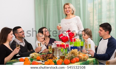 Happy relatives proposing a toast for family member with gifts at home celebration