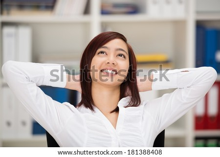 Happy relaxed Asian businesswoman daydreaming sitting at her desk in the office with her hands clasped behind her head and a beautiful smile - stock photo