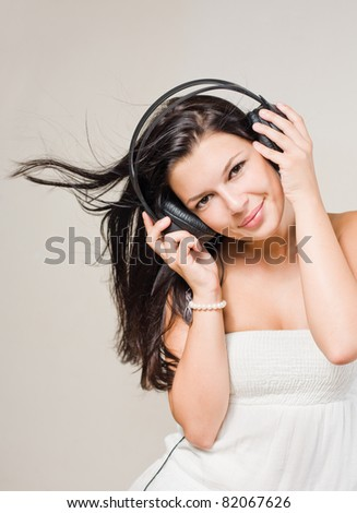 Happy relaxed brunette listening to music wearing headphones.