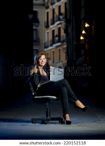 Happy relaxed Business woman office dressed sitting on Chair giving an ok sign outdoors on Street with Computer laptop in successful and flexible worker concept on studio lighting  - stock photo