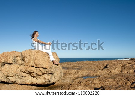 Happy relaxed confident attractive mature woman sitting on rock overlooking the ocean, isolated with blue sky as background and copy space. - stock photo