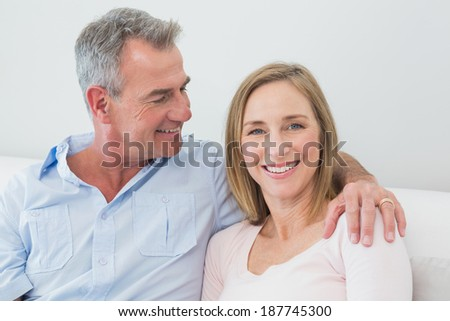 Happy relaxed couple sitting on sofa with arm around at home - stock photo