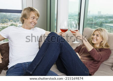 Happy relaxed couple toasting wine glasses in living room at home - stock photo
