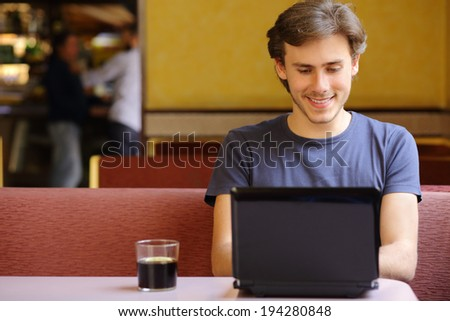 Happy relaxed man browsing social media surfing internet on a laptop in a restaurant            - stock photo