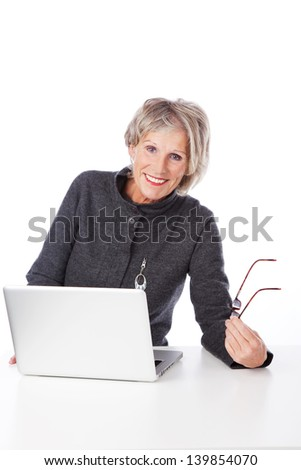 Happy relaxed modern senior woman using a laptop computer sitting at a table holding her reading glasses in her hand - stock photo