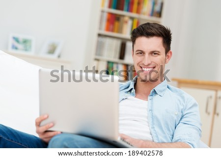 Happy relaxed young man with a friendly smile sitting on a sofa at home working on his laptop computer - stock photo