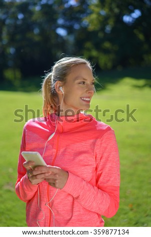 Happy relaxed young woman listening to music on her mobile phone outdoors in a lush green park turning to watch something behind her with a smile