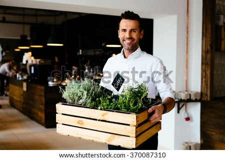 Happy restaurant manager holding box with fresh spices - stock photo