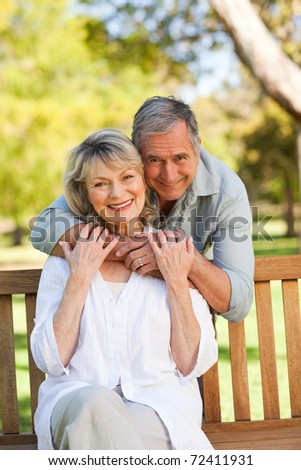Happy retired couple sitting on the bench - stock photo