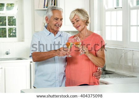 Happy retired couple toasting white wine while standing in kitchen - stock photo