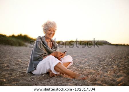 Happy retired woman sitting relaxed on beach holding a mobile phone in hand. Senior caucasian woman with cell phone on the beach outdoors - stock photo