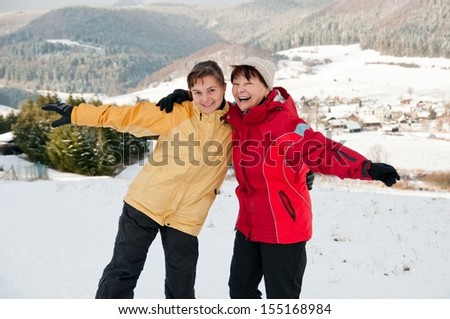 Happy retirement - mother and daughter in winter - stock photo