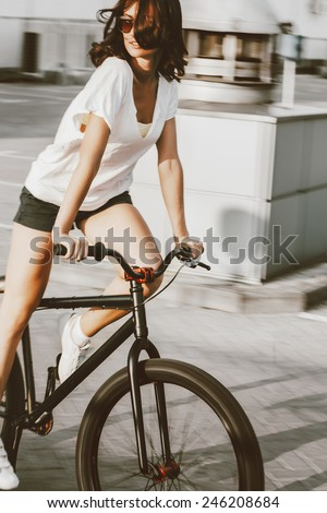 Happy riding girl on street bicycle. Motion blur - stock photo