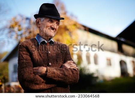 Happy Romanian senior farmer near a traditional house, at sunset - stock photo