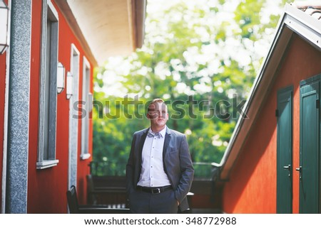 Happy romantic blond handsome groom in grey suit outside hotel - stock photo