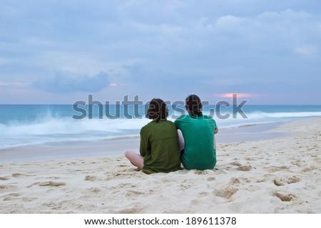 Happy romantic couple enjoying beautiful stormy sunset on the beach at coastline of Sri Lanka, Ceylon - stock photo