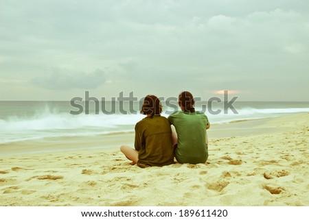 Happy romantic couple enjoying beautiful stormy sunset on the beach at coastline of Sri Lanka, Ceylon. Vintage style toned image - stock photo