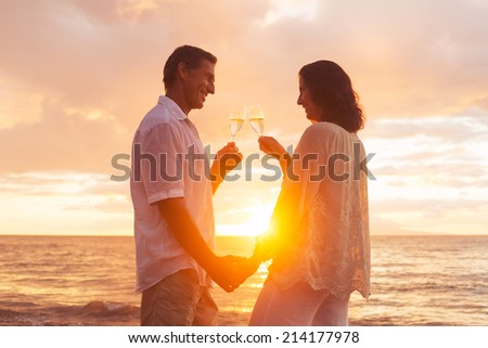 Happy Romantic Couple Enjoying Glass of Champagne at Sunset on the Beach. Vacation Travel Retirement Anniversary Celebration. - stock photo