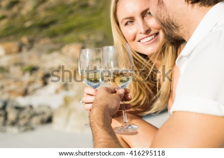 Happy romantic couple enjoying glass of white wine on the beach. Cheerful couple toasting wineglasses for celebrating anniversary. Close up of couple toasting with white wine outdoor. - stock photo