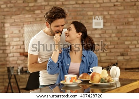 Happy romantic couple having breakfast together, feeding each other. - stock photo