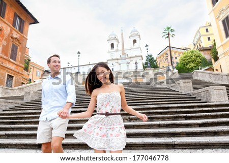 Happy romantic couple holding hands on Spanish Steps in Rome, Italy. Joyful young interracial couple walking on the travel landmark tourist attraction icon during their romance Europe holiday vacation - stock photo