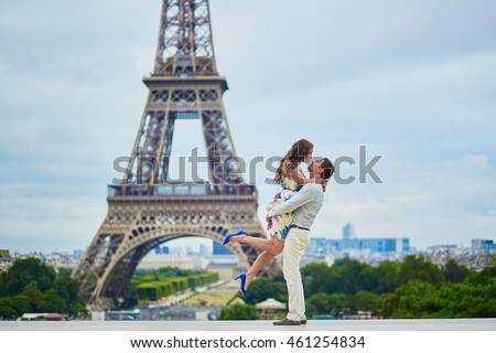Happy romantic couple hugging near the Eiffel tower in Paris, girl is jumping, Tourists enjoying their vacation to France
