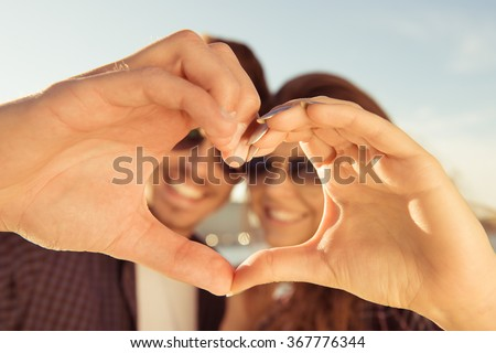 Happy romantic couple in love gesturing a heart with fingers - stock photo