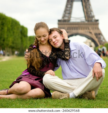 Happy romantic couple in Paris, sitting on grass by the Eiffel Tower - stock photo