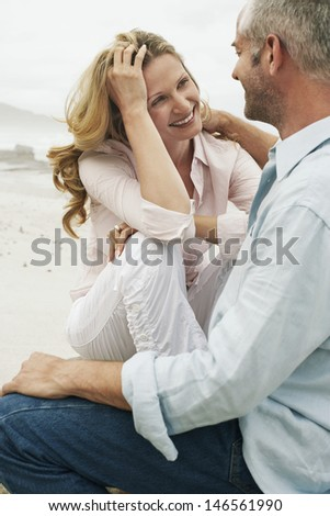 Happy romantic couple looking at each other while sitting on beach