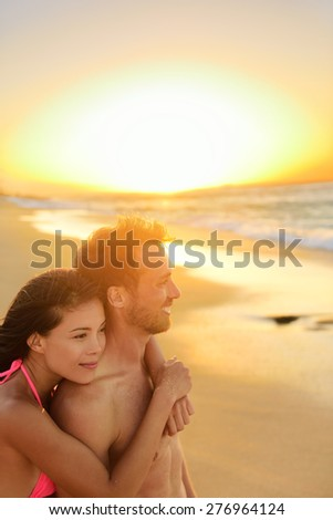 Happy romantic couple lovers on beach honeymoon having playful fun together during summer beach holidays. Cheerful young multiracial couple, Asian woman and Caucasian man. From Oahu, Hawaii, USA. - stock photo