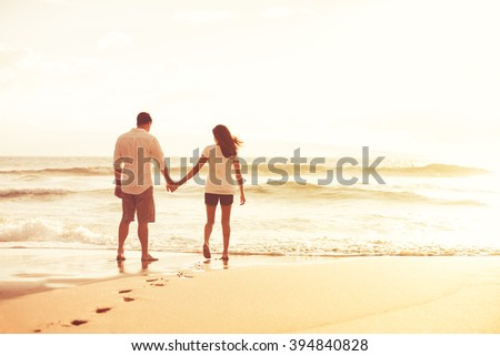 Happy romantic couple on the beach at sunset. Young lovers on vacation. - stock photo