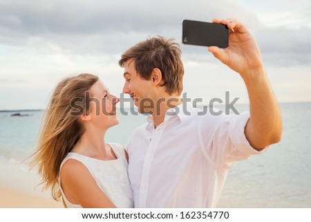 Happy romantic couple on the beach taking photo of themselves with smart phone at sunset, Man and woman in love  - stock photo