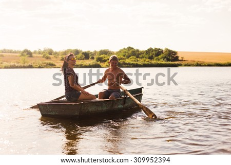 Happy romantic couple rowing a boat on lake. - stock photo