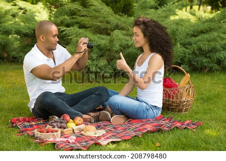 Happy romantic couple taking pictures on picnic