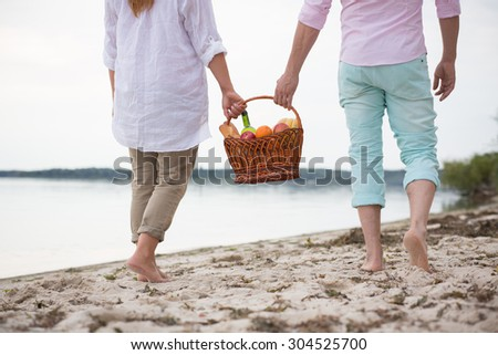 Happy romantic couple walking on the sand at the beach after picnic. They both holding basket full of food and drinks. - stock photo