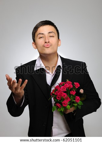 Happy romantic husband holding rose flower and vine bottle prepared to celebrate. gray background - stock photo