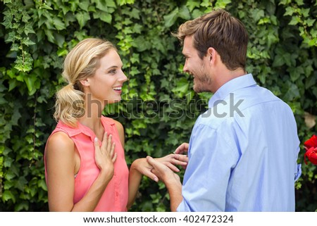 Happy romantic man wearing ring to woman at front yard