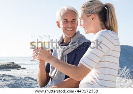 Happy romantic mature couple enjoying glass of white wine on the beach. Cheerful senior couple raising a toast celebrating wedding anniversary.  - stock photo
