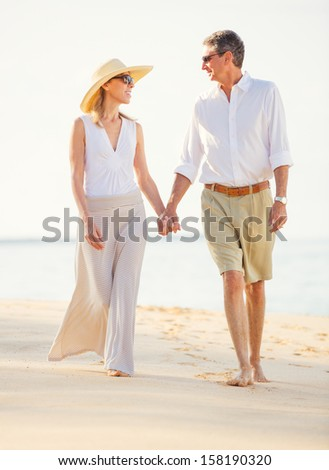 Happy Romantic Middle Aged Couple Enjoying Walk on the Beach - stock photo