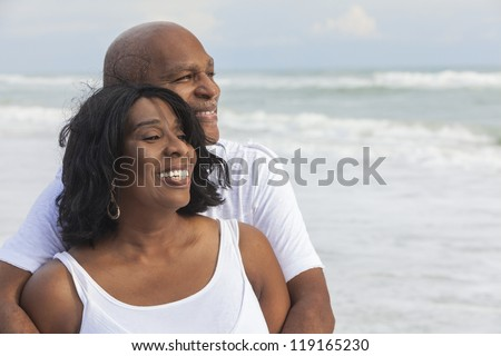 Happy romantic senior African American man and woman couple on a deserted tropical beach - stock photo