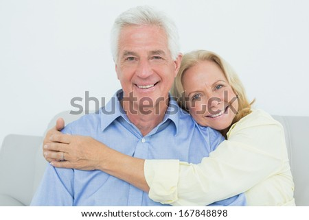Happy romantic senior couple sitting on sofa in a house - stock photo
