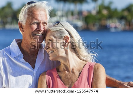 Happy romantic senior man and woman romantic couple together embracing by tropical sea or river - stock photo