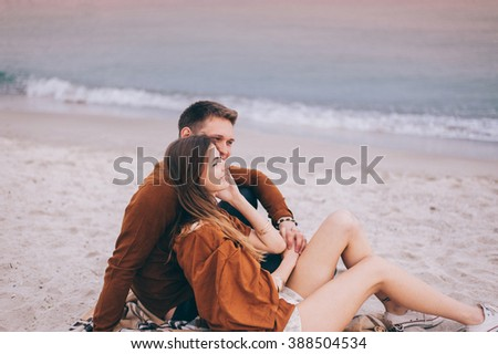 Happy romantic teenage couple smiling enjoying of beautiful vanilla sky at the sea beach. Wearing trendy clothes. Travel vacation. Lifestyle Concept - stock photo