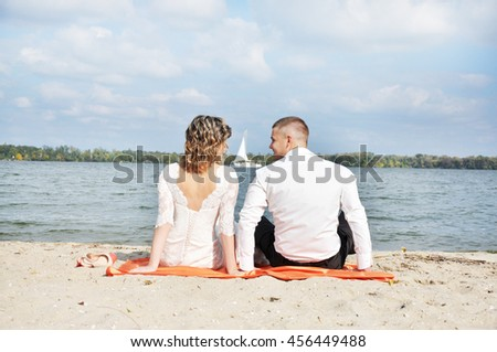 happy romantic wedding couple in love, men and women in white wedding dress sitting on the beach and look at the horizon