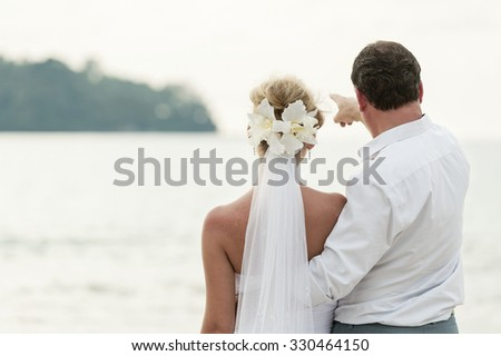happy romantic wedding couple in love, men and women in white wedding dress walk on the beach and look at the horizon - stock photo