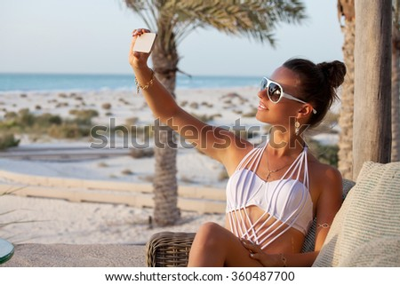 Happy Romantic Woman Enjoying Beautiful Sunset at the Beach, taking selfie. Outdoors lifestyle portrait. Summer luxury vacation. - stock photo