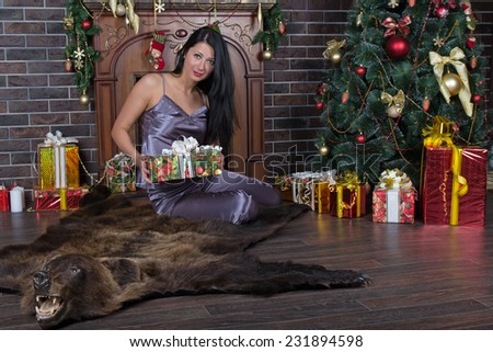 Happy romantic woman sitting under Christmas tree on bearskin with pile of Christmas presents - stock photo