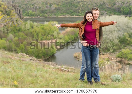 Happy romantic young couple celebrating an enjoyable day out in the countryside with the man hugging the woman from behind as she smiles with outstretched arms overlooking a scenic valley and river - stock photo